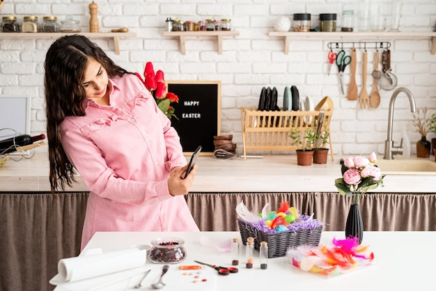Piękna brunetka kobieta robienie zdjęć zdobionych pisanek przy użyciu telefonu komórkowego w kuchni