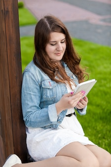 Piękna brunetka kobieta siedzi na trawie w parku i używa tabletu
