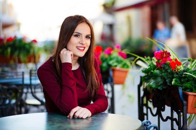 Piękna brunetka kobieta siedzi w kawiarni w paryżu