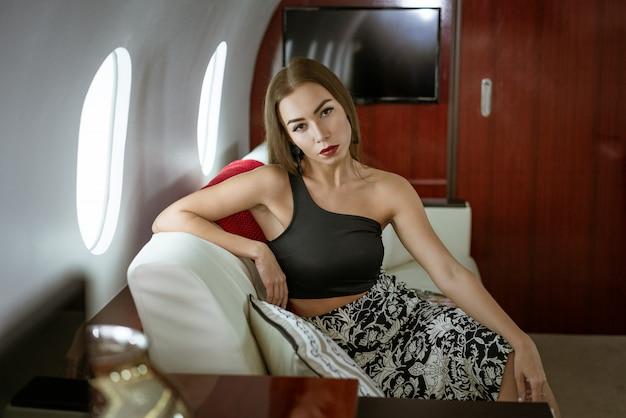 Piękna brunetka kobieta siedzi w prywatnym fotelu samolotu