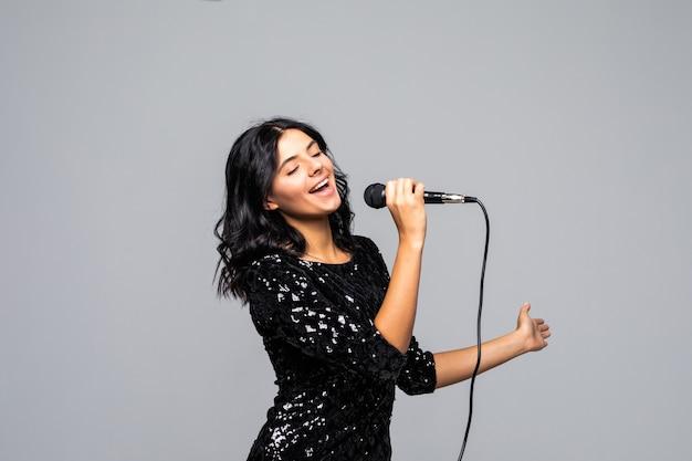 Piękna brunetka kobieta śpiewa do mikrofonu na szarej ścianie