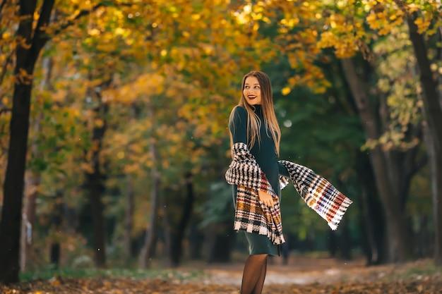 Piękna brunetka kobieta ubrana w ciepły szal z dzianiny, cieszący się spacerem po jesiennym parku przyrody