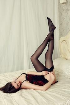Piękna brunetka kobieta ubrana w czarną bieliznę w łóżku