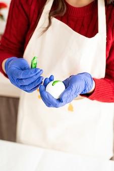 Piękna brunetka kobieta w czerwonym swetrze i białym fartuchu, barwiąc pisanki w rurce otwierania kuchni z kolorowym płynem
