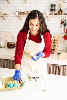 Piękna brunetka kobieta w czerwonym swetrze i białym fartuchu, kolorując pisanki w kuchni