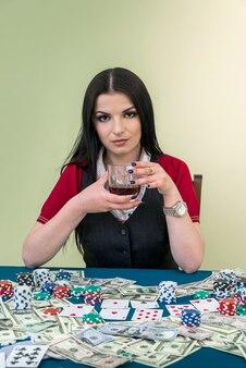 Piękna brunetka kobieta w kasynie ze szklanką napoju