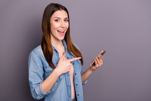 Piękna brunetka kobieta w koszuli dżinsy pozuje z jej telefonem na fioletową ścianę