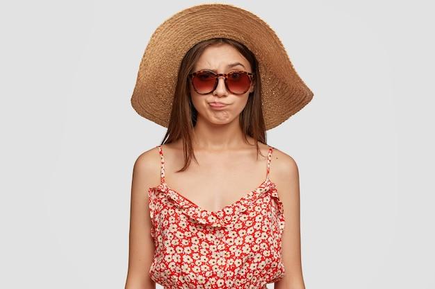 Piękna brunetka kobieta w letnim kapeluszu, sukience, zaciska usta z niezadowoleniem, czuje niezadowolenie