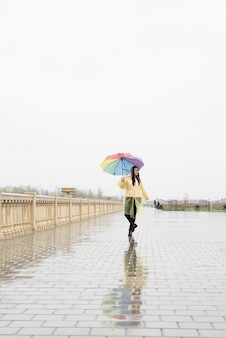 Piękna brunetka kobieta w żółtym płaszczu przeciwdeszczowym trzymająca tęczowy parasol w deszczu