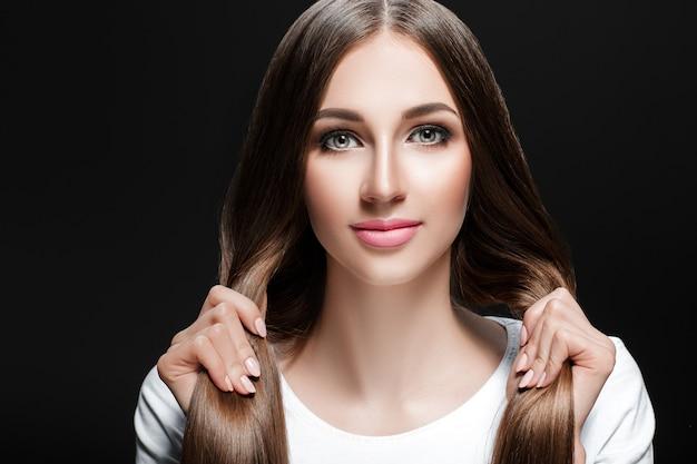 Piękna brunetka kobieta z błyszczącymi prostymi długimi włosami. pielęgnacja włosów