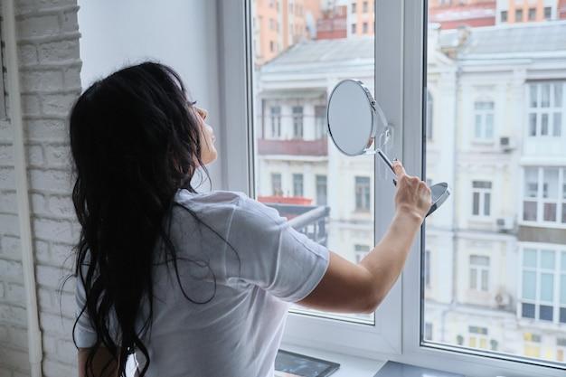 Piękna brunetka kobieta z długimi falowanymi włosami podziwia siebie w lustrze