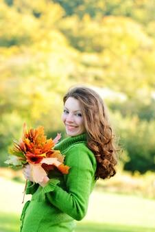 Piękna brunetka kobieta z liśćmi klonu, jesienne tło z miejsca na kopię