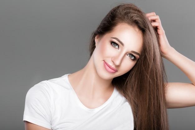 Piękna brunetka kobieta z lśniące proste długie włosy patrzy w kamerę. pielęgnacja włosów