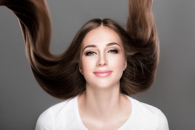 Piękna brunetka kobieta z przepięknymi błyszczącymi długimi włosami latania. pielęgnacja włosów