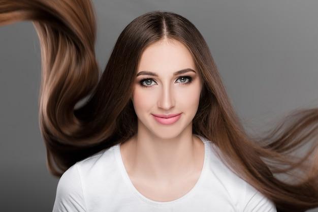 Piękna brunetka kobieta z przepięknymi lśniącymi długimi włosami latającymi patrzy w kamerę. pielęgnacja włosów