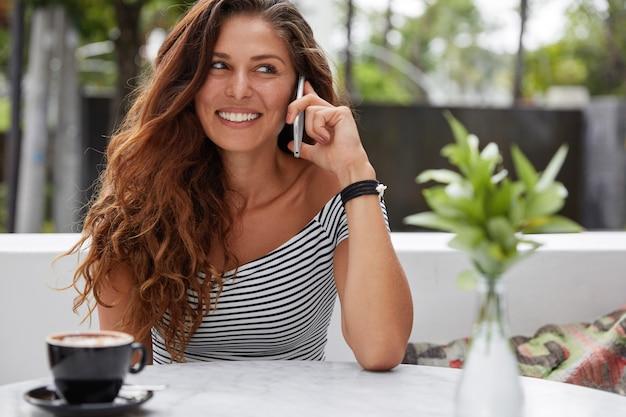 Piękna brunetka kobieta z zadowolonym wyrazem i telefonem w kawiarni na świeżym powietrzu na tarasie