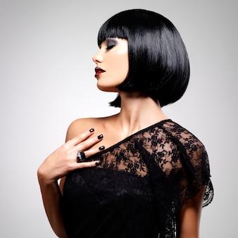 Piękna brunetka kobieta z zastrzeloną fryzurą, portret zbliżenie modelki