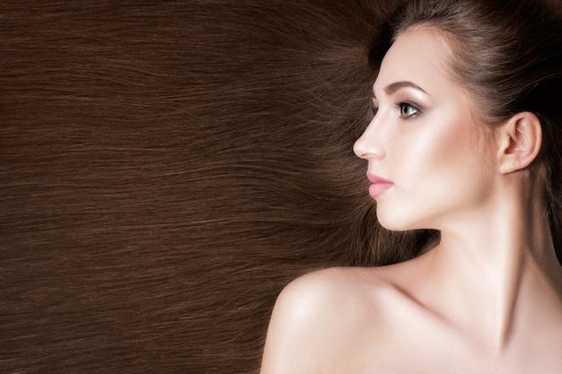 Piękna brunetka kobieta ze zdrowymi długimi włosami