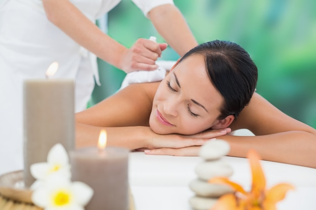 Piękna brunetka korzystających masaż ziołowych kompresji