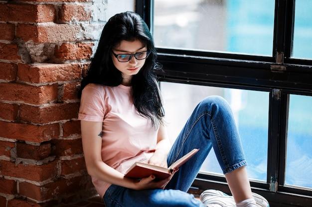 Piękna brunetka młoda kobieta czytanie książki przy oknie w domu.