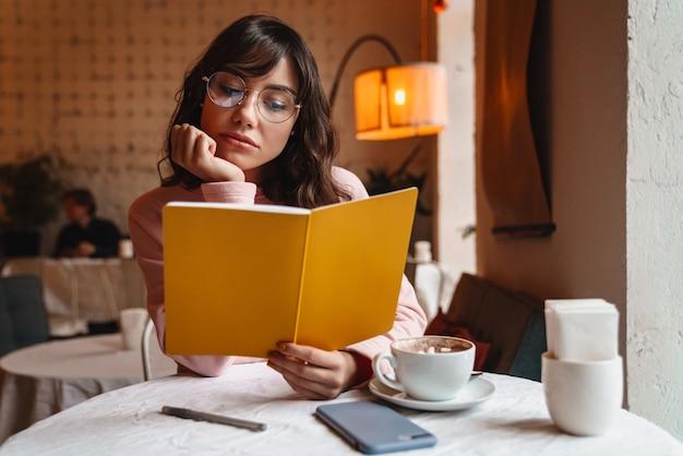 Piękna brunetka młoda kobieta w pomieszczeniu w kawiarni czytanie książki.