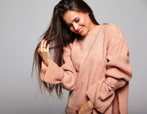 Piękna brunetka model w swobodnym beżowym ciepłym swetrze bawiącym się włosami