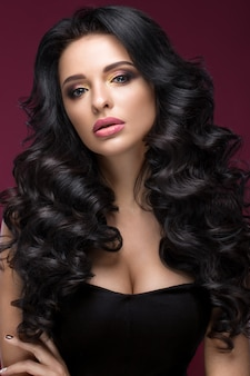 Piękna brunetka modelka: loki, klasyczny makijaż, złota biżuteria i czerwone usta. piękna twarz.