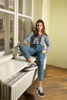 Piękna brunetka modelka w niebieskiej koszuli i dżinsach na parapecie