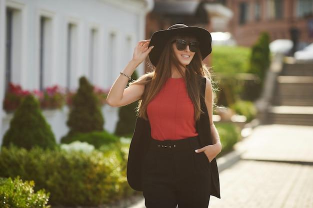 Piękna brunetka modelka z idealnym ciałem w czerwonej bluzce i modnym czarnym garniturze dostosowującym swój stylowy czarny kapelusz, uśmiecha się i pozuje na słonecznej ulicy miasta