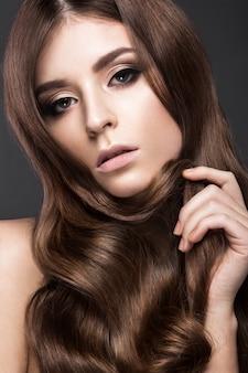 Piękna brunetka o idealnie kręconych włosach i klasycznym makijażu