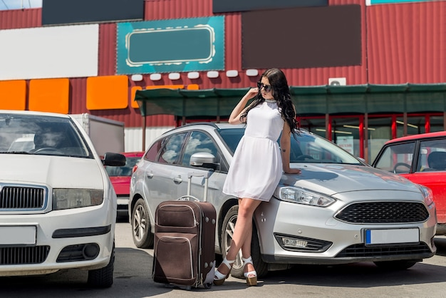 Piękna brunetka podróżująca z walizką w samochodzie