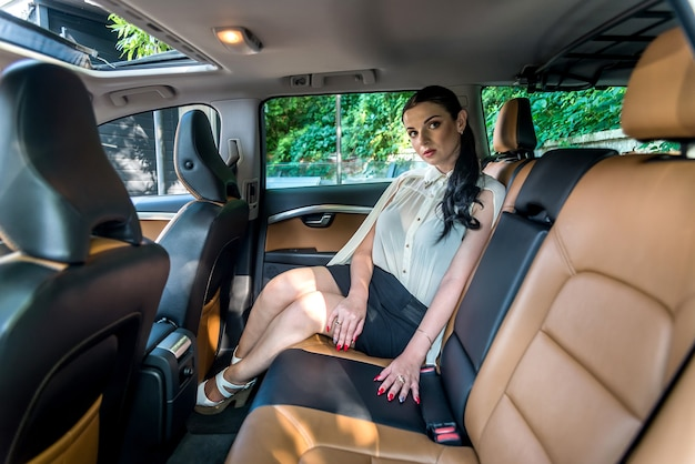 Piękna brunetka pozuje na tylnym siedzeniu samochodu