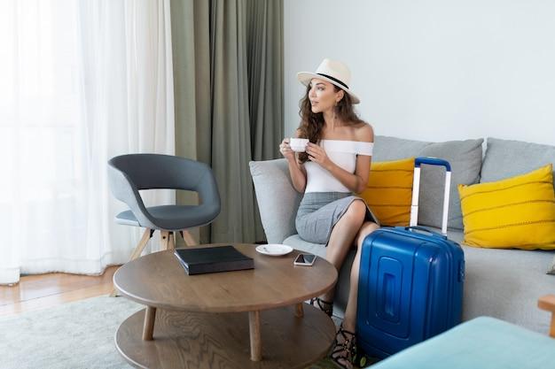 Piękna brunetka pozuje siedząc na szarej kanapie w białej koszulce, szarej spódnicy, jasnym kapeluszu z filiżanką kawy w dłoni, obok której stoi niebieska walizka