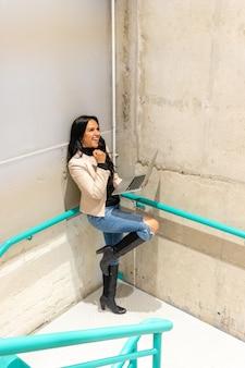 Piękna brunetka pracuje ze swoim laptopem ze schodów
