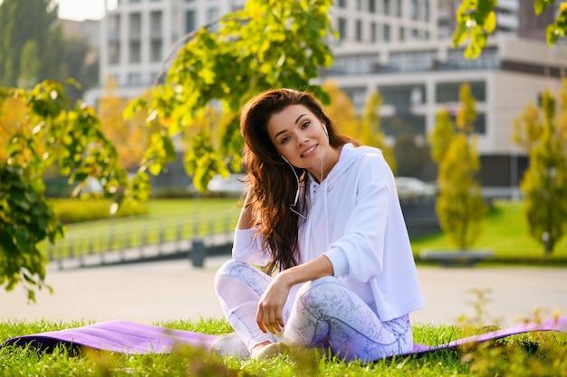 Piękna brunetka relaksuje się na macie sportowej na tle zielonego parku miejskiego w białej bluzie z kapturem i legginsach, słuchaj muzyki w słuchawkach