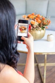 Piękna brunetka robi zdjęcie słodkiego bukietu kwiatów w dyni pomalowanej kapustą.