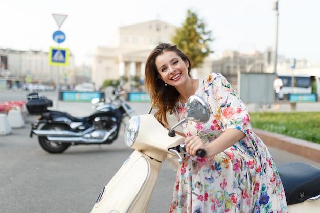 Piękna brunetka siedzi na motocyklu