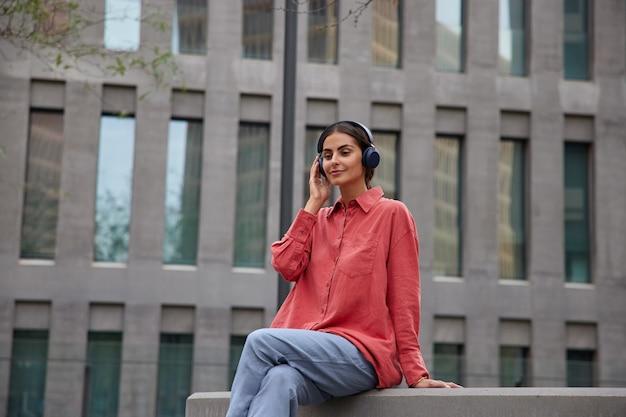 Piękna brunetka siedzi na zewnątrz, słucha muzyki lub podcastu audio przez bezprzewodowe słuchawki, lubi spędzać wolny czas, ubrana w czerwoną koszulę i spodnie, robi sobie przerwę po spacerze