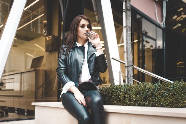 Piękna brunetka siedzi w pobliżu centrum biznesowego i pali vape