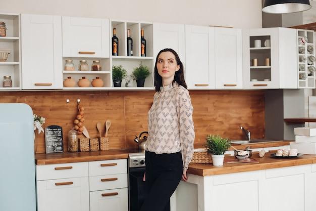 Piękna brunetka stoi w kuchni. wzorzysta bluzka i ciemne spodnie lub dżinsy stojące w nowoczesnej kuchni i odwracające wzrok w zamyśleniu..