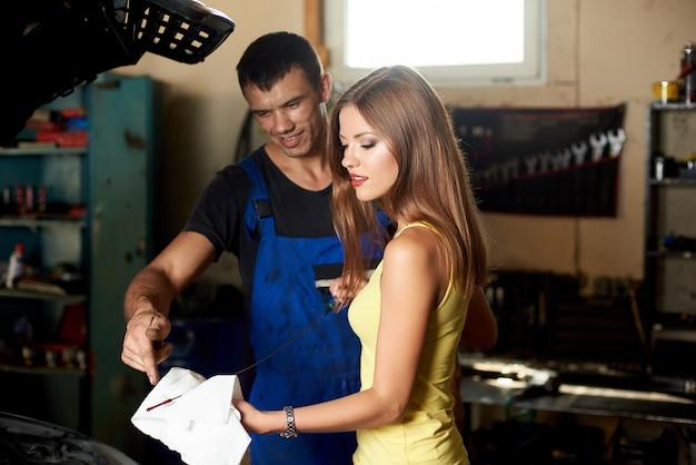 Piękna brunetka trzyma bagnet, aby sprawdzić olej silnikowy, który mówi jej mechanik, oboje stoją w pobliżu otwartej maski samochodu w garażu