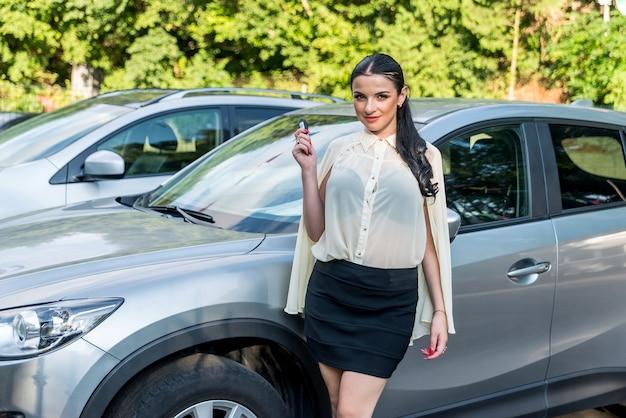 Piękna brunetka trzyma klucz od nowego samochodu
