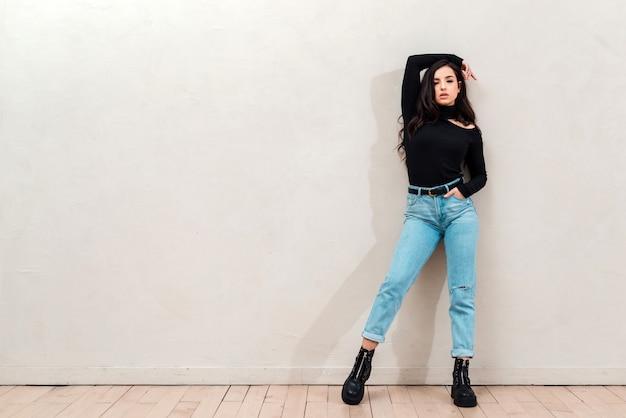 Piękna brunetka ubrana w czarny materiał, rzuca dłoń na głowę i pozuje. koncepcja moda, miejsce na reklamę, lato