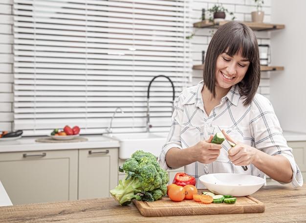 Piękna brunetka, uśmiechając się i przygotowując sałatkę na niewyraźne tło wnętrza kuchni.
