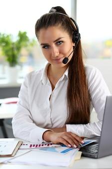Piękna brunetka uśmiechający się urzędnik call center w pracy
