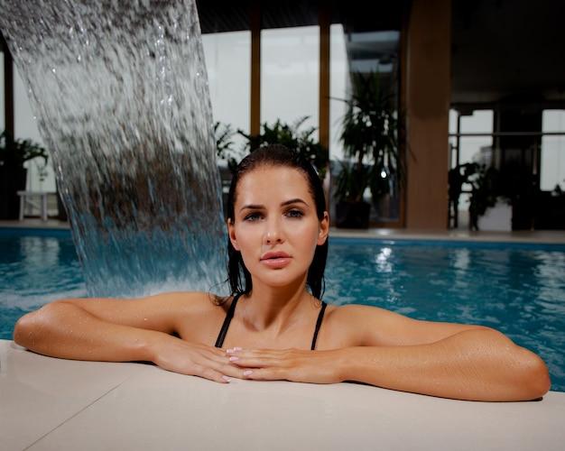 Piękna brunetka w basenie odpoczywa