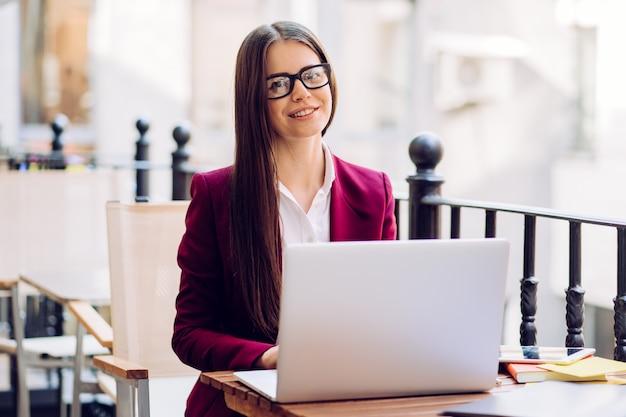 Piękna brunetka w bordowym garniturze i białej koszuli siedzi przy stole, pracując w kawiarni na świeżym powietrzu z czule uśmiechniętym laptopem.