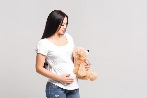 Piękna brunetka w ciąży kobieta w białej koszuli i dżinsach na białej ścianie z misiem-zabawką w rękach