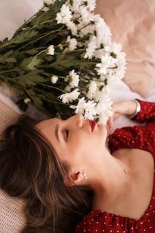Piękna brunetka w czerwonej sukience leży na łóżku obok bukietu stokrotek. portret pięknej kobiety.