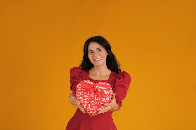Piękna brunetka w czerwonej sukience trzyma w dłoniach pudełko w kształcie serca